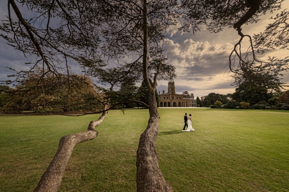 Leading tree branches to walking couple on wedding with a mood sky and Werribee mansion in the background