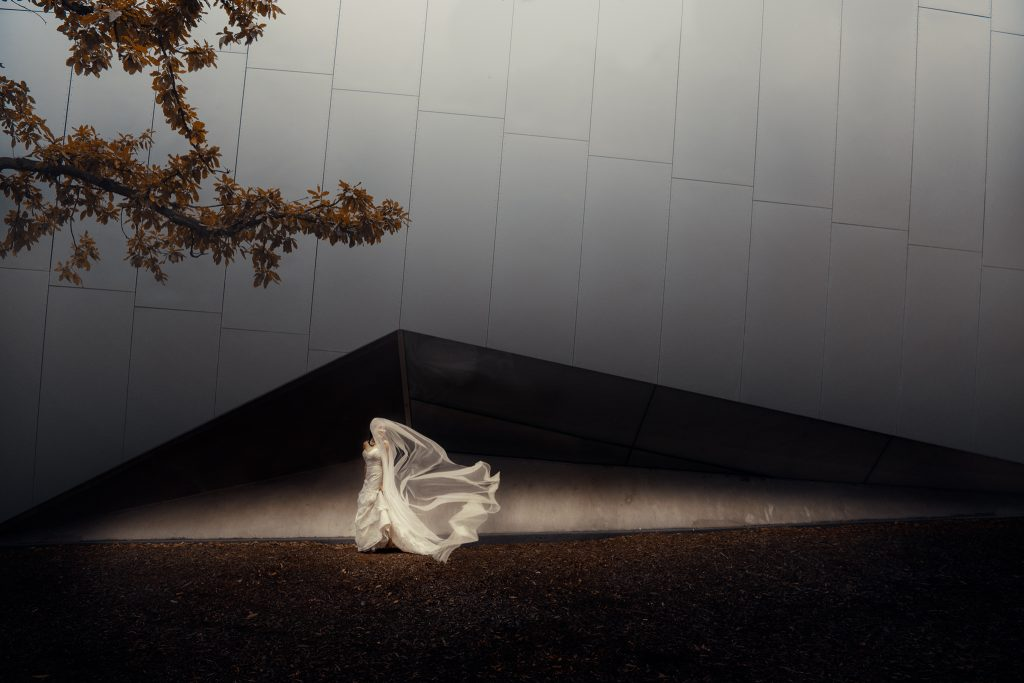 Bride looking over shoulder with veil blowing over her face framed within the triangle shape of the Melbourne museum building