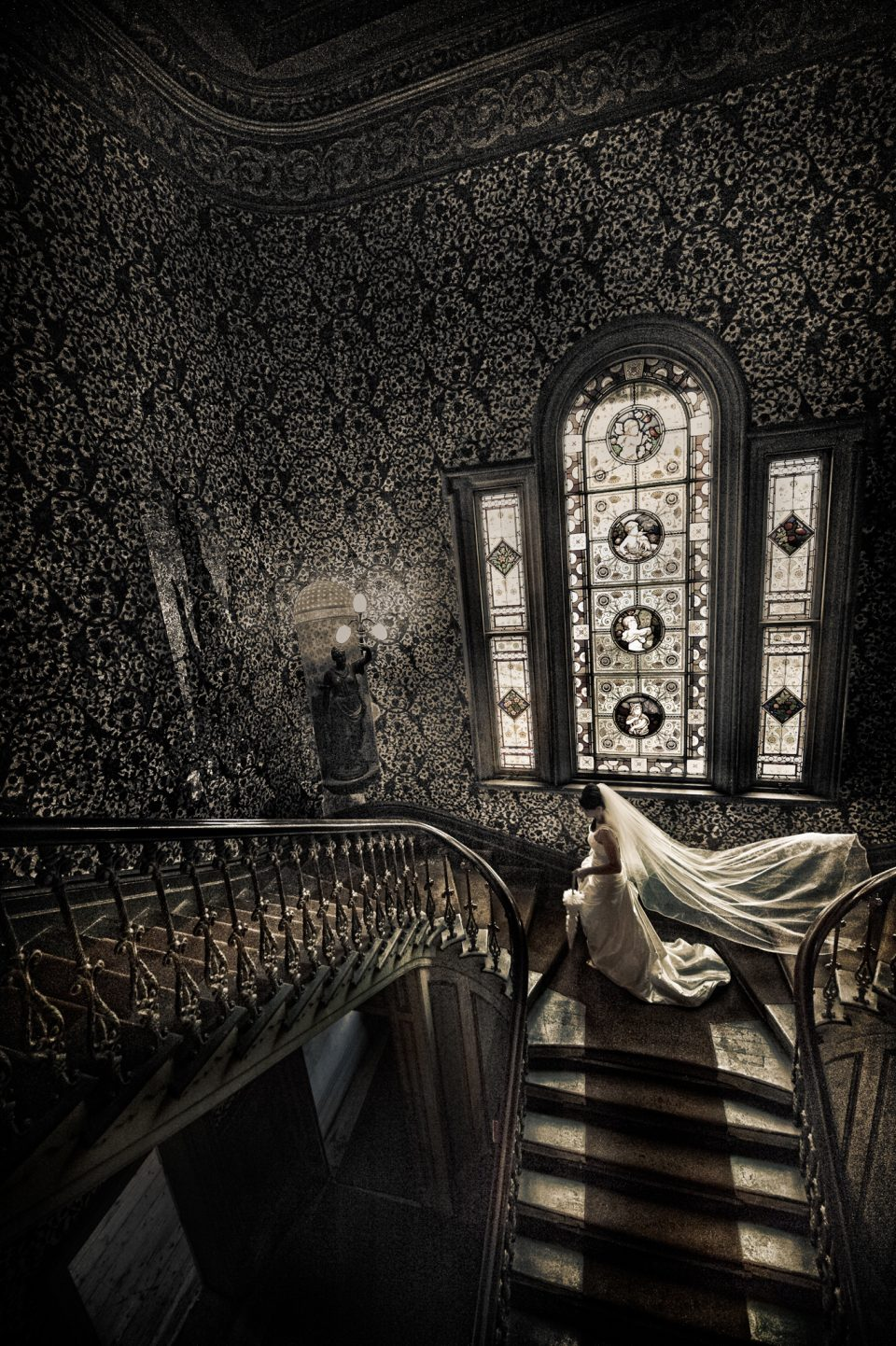 Bride captured walking from grand staircase with opulent leadlight windows and gilt embossed wallpaper as veil drifts behind her