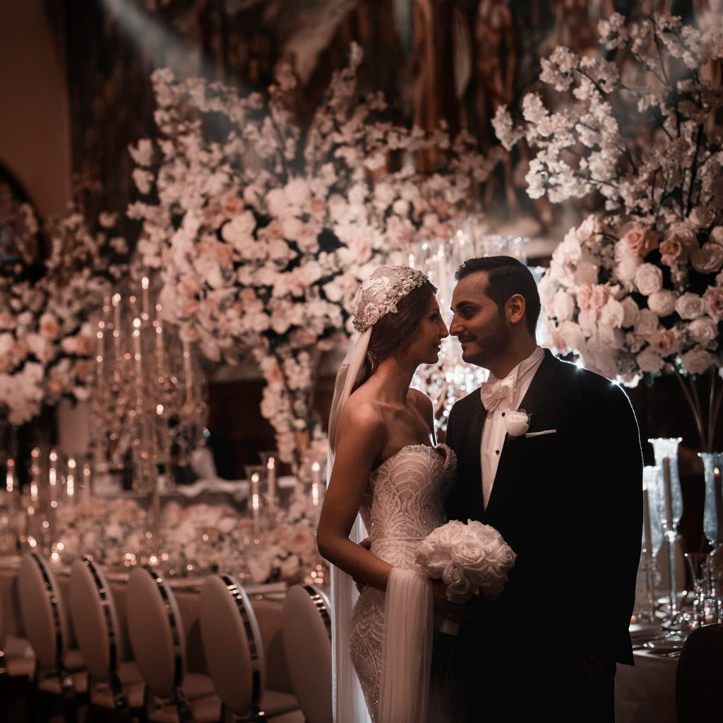 Wedding photo of couple looking at each other surrounded by flowers styled by John Emanuel at Sydney University