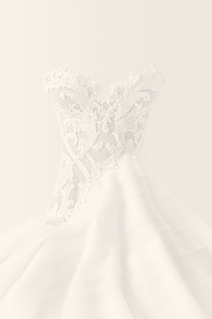 White strapless embroidered wedding dress photographed on a white wall for a detail shot on wedding day