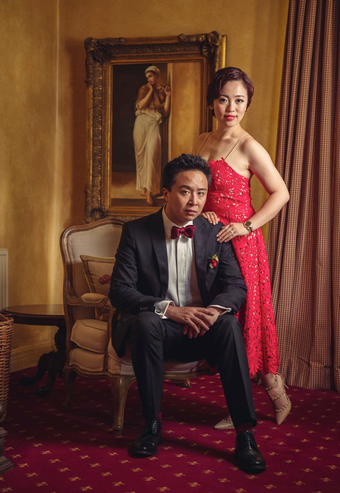 Groom on chair with bride standing, dressed in red posing for a wedding photo with ornately framed painting in background at wedding venue Milton park