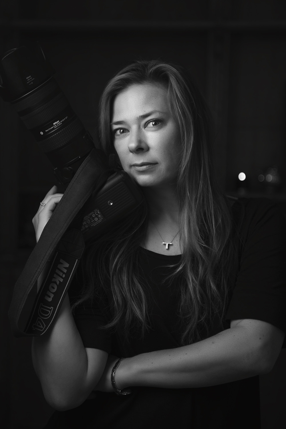 black and white photo of melbourne photographer Tanya wilson photographer posing with camera near face