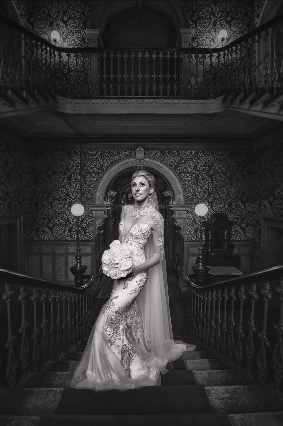 Black and white photograph of bride posed at the top of staircase at Labassa Maison Melbourne on wedding day holding her bouquet of flowers