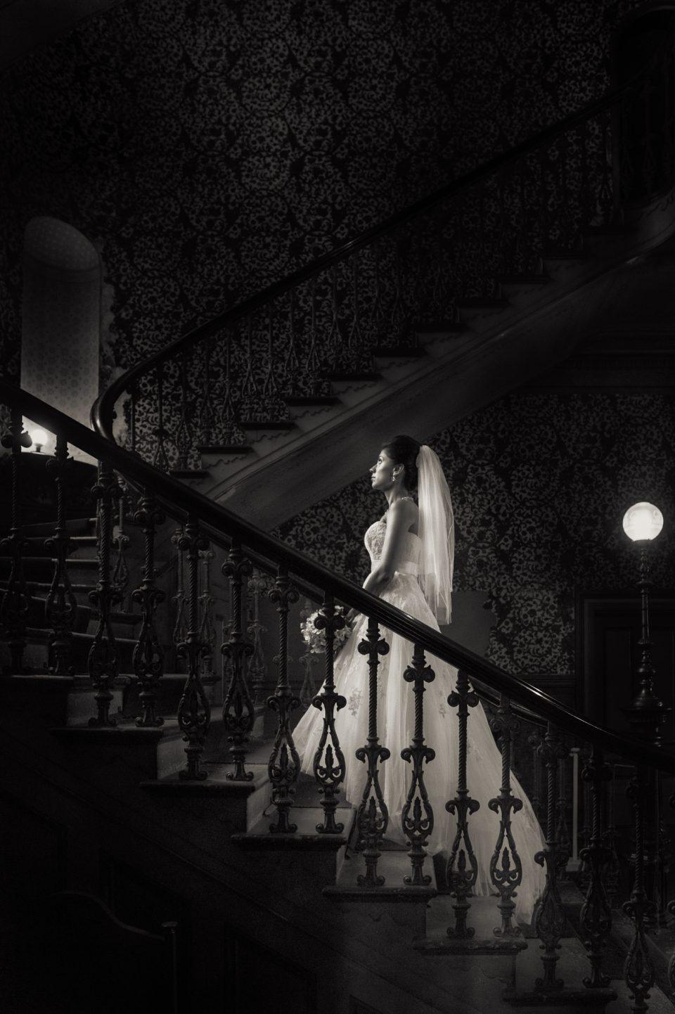 Bride walks up grand stair case at Labassa mansion towards light