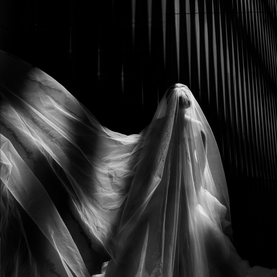 Black and white photo of the back of bride with veil blowing to the left with bright light streaming through
