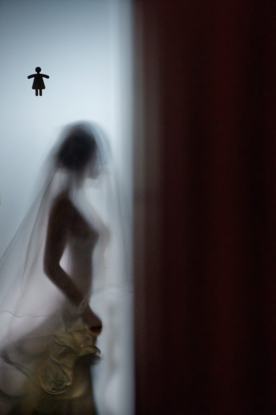 Profile of bride photographed through an opaque door with small icon of a lady above her at eureka tower