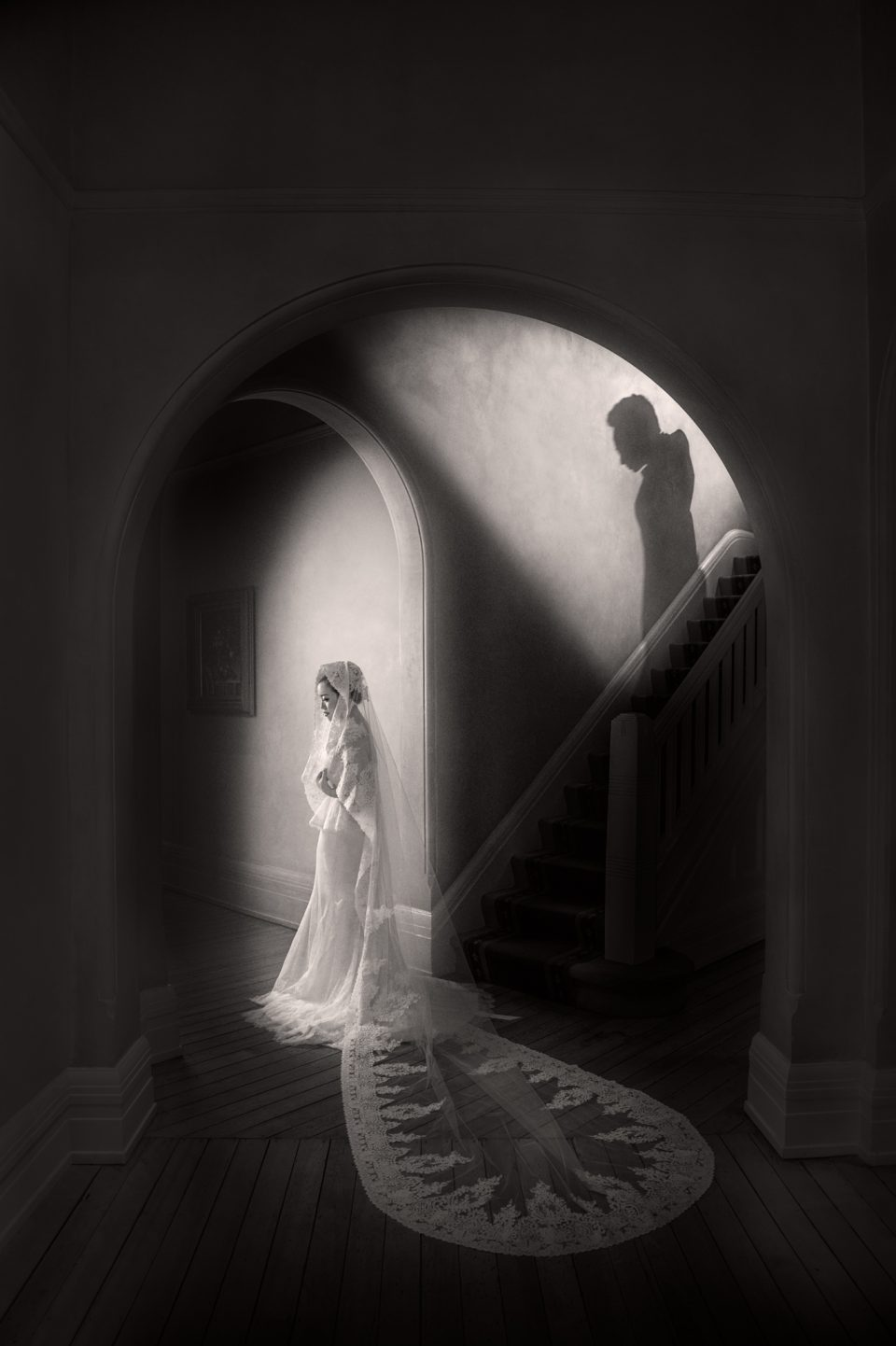 Bride stands in archway as the shadow of her groom a seen coming down the stairs at wedding reception in Bowral