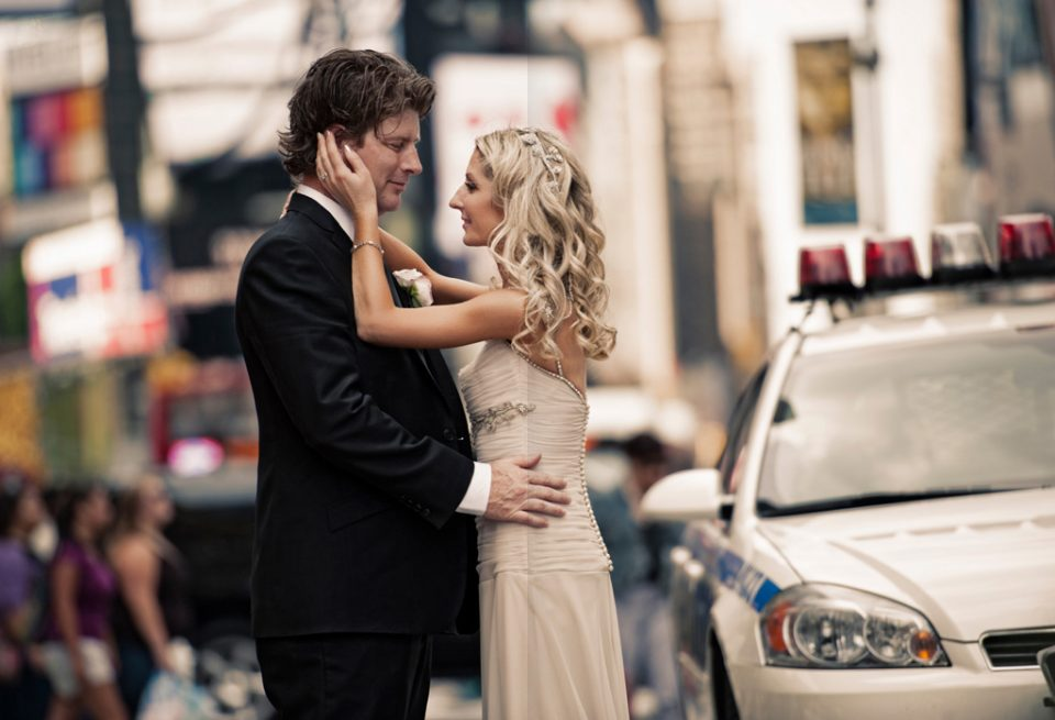 Wedding couple stand looking at each other with bides hand softly placed on grooms face with time square in background and New York City police car on right