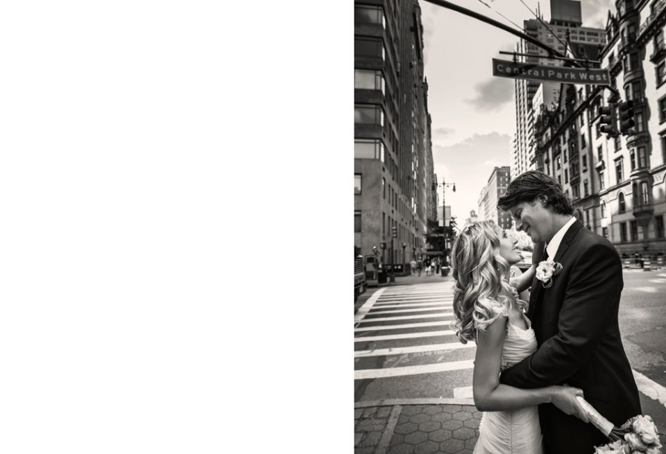 destination wedding photo of bride and groom looking at each other, standing on street corner with central park west signage above them in New York