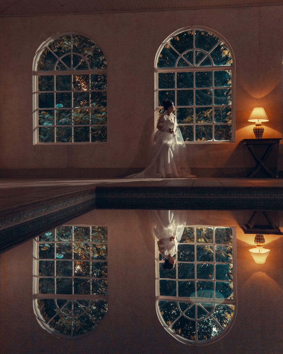 Bride sits by arched windows lit by lamp with reflection of her and windows in pool at Milton Park Country House in Bowral