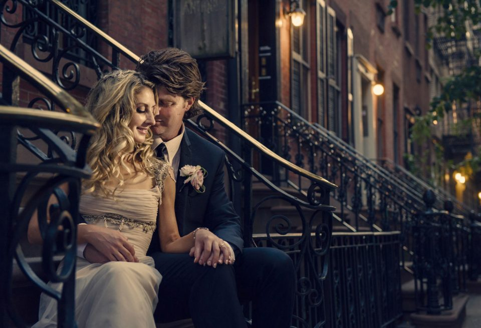 Happy moment of bride leaning into groom while sitting on stairs at dusk on the streets of New York on their wedding day
