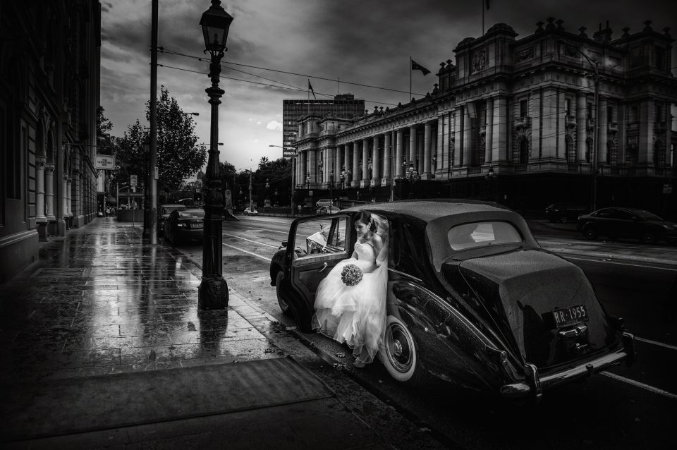 Bride in white wedding dress getting out of black Rolls Royce at the Windsor Hotel Melbourne on a rainy day with Parliament House in background