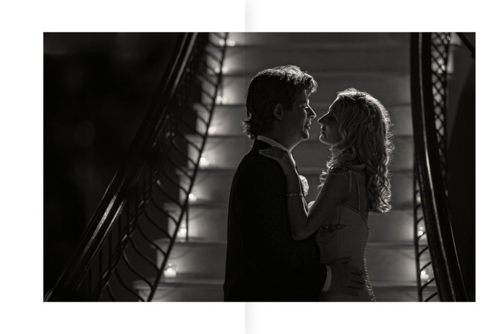 Black and white photo taken inside of bride and groom looking at each other, framed by background of a staircase on their wedding day