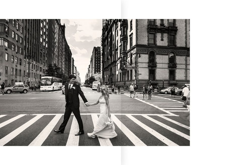 Groom leads bride dressed in sneakers, across a pedestrian crossing on the busy streets of New York on their wedding day
