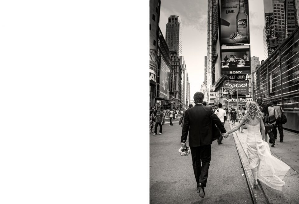 Black and white image of bride and groom holding hands walking away from the camera, in Time Square for their New York destination wedding