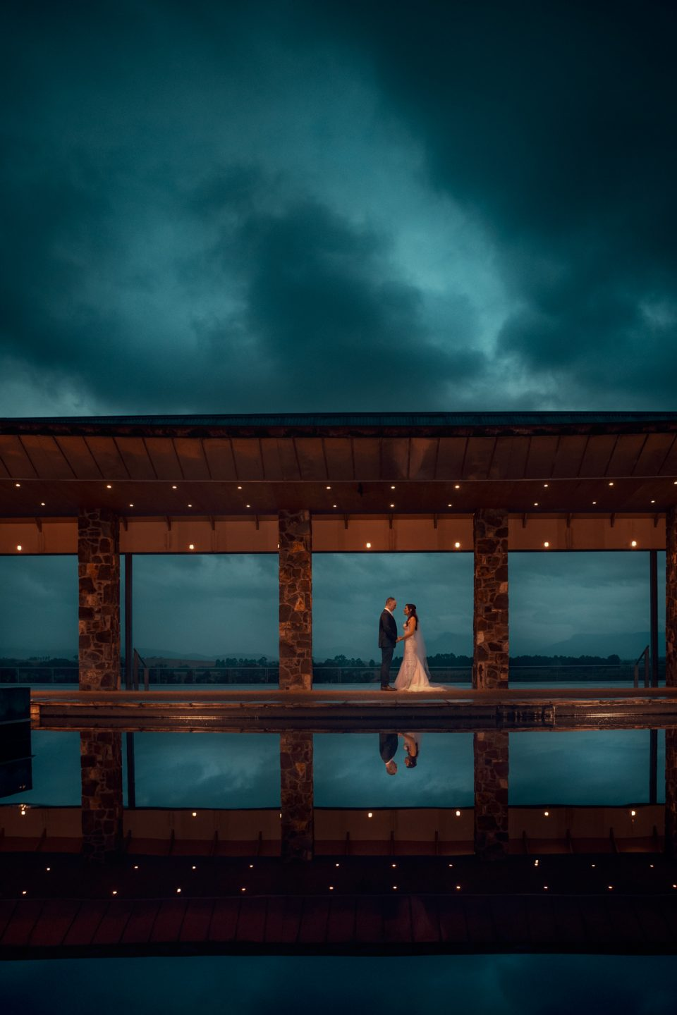 Couple stand in open passageway with dark moody blue sky above on wedding day at Yering Station Winery