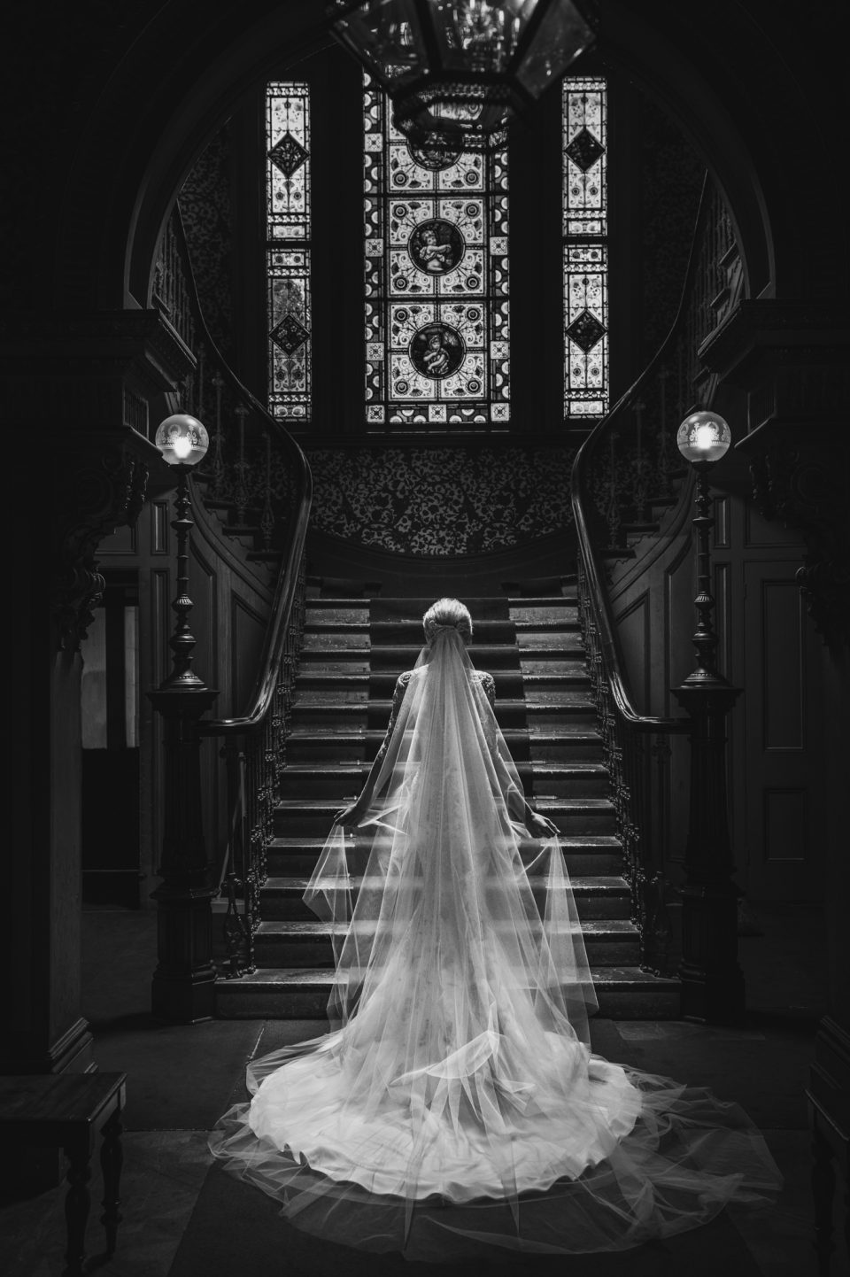 Back of bride as she walks up grand staircase towards opulent leadlight windows of Labassa mansion