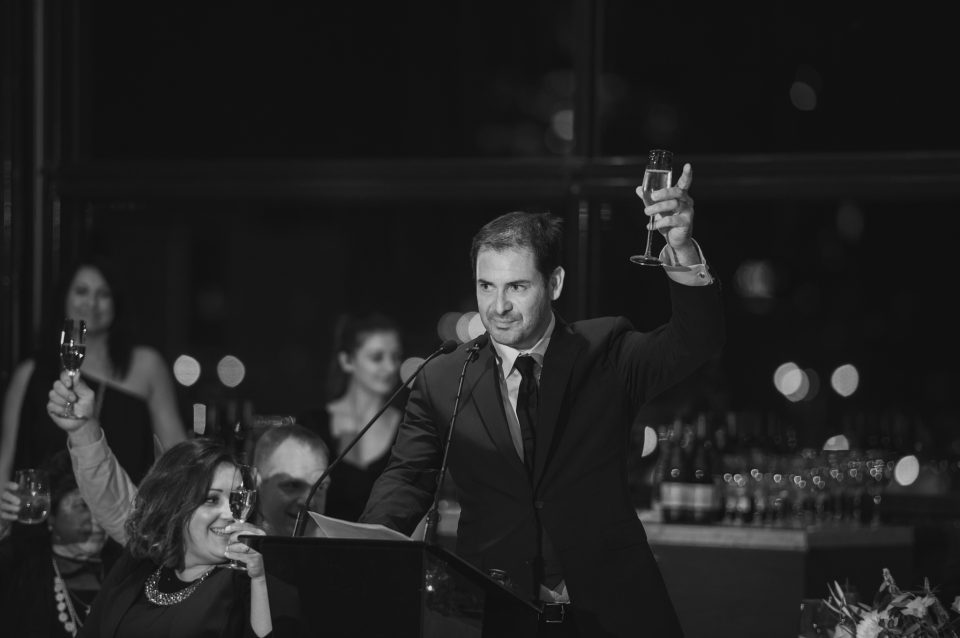 Black and white photo candidly taken during speech as he raises glass at wedding venue in Melbourne, Luminare