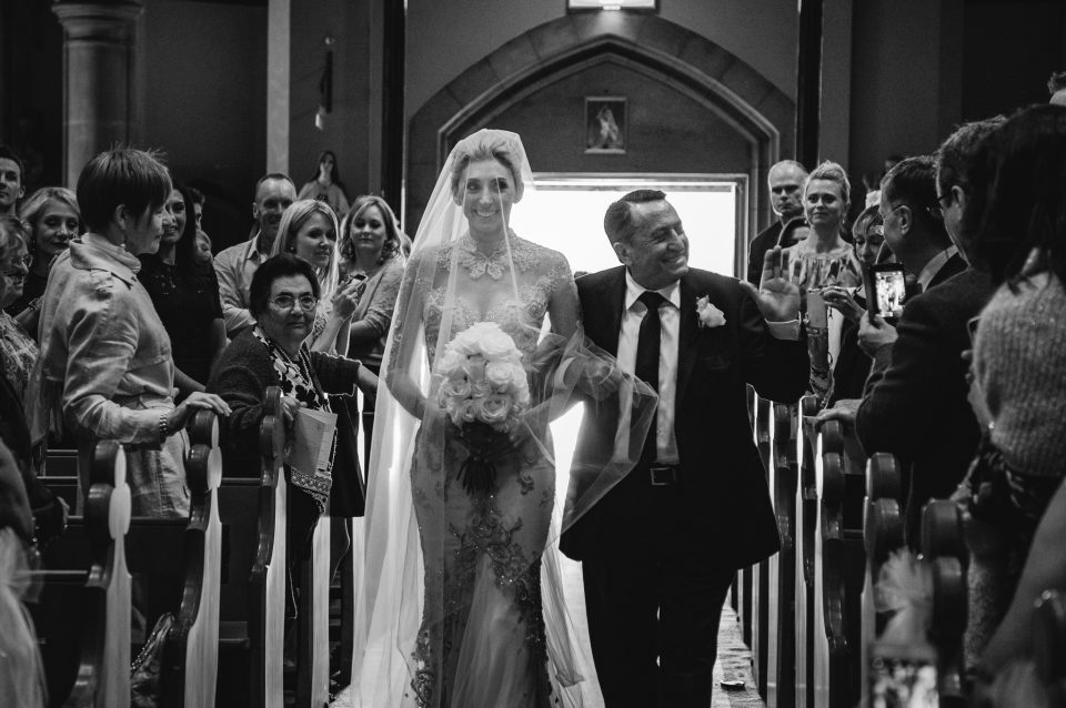 Proud father waves at guests as he walks his daughter down the church isle as both smile.