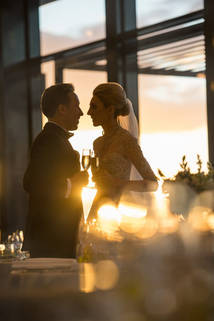 Sunset silhouette of bride and groom looking at each other holding champagne glasses inside their wedding reception Luminaire in South Melbourne