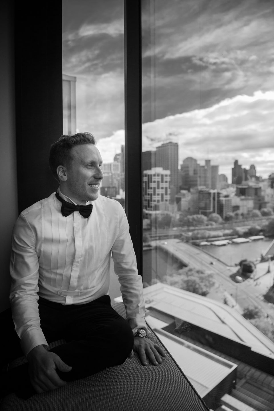 Groom sitting by window at Crown Towers overlooking the view of Melbourne prior to his wedding
