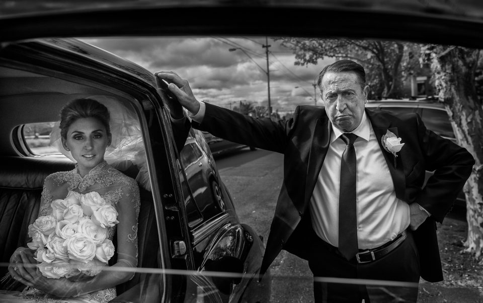 Grumpy father of the bride leaning against car waiting for the bride to get out of the black wedding car at St Johns Church in Clifton Hill Melbourne