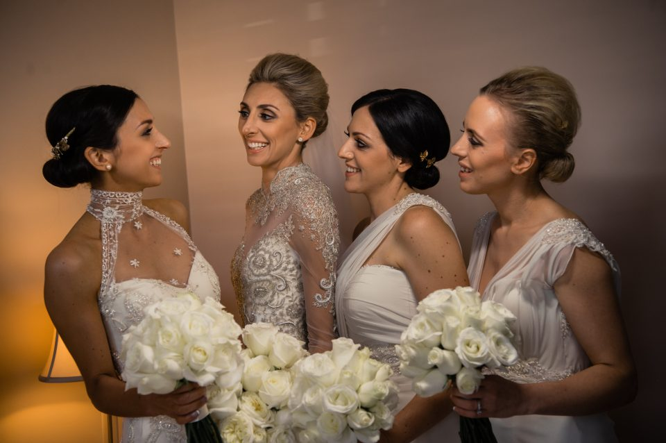 Happy photo of bride and bridesmaids looking at each other holding bouquets of white roses
