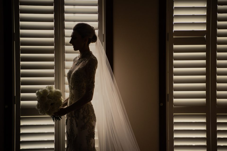 Bride silhouette in window that has white planation blinds closed creating interesting horizontal lines of light