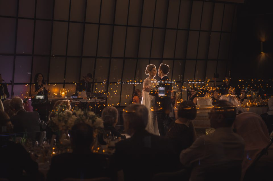 Candid photo of Wedding couples first dance seen through windows of Luminare reception with refection of the Melbourne city scape with guests