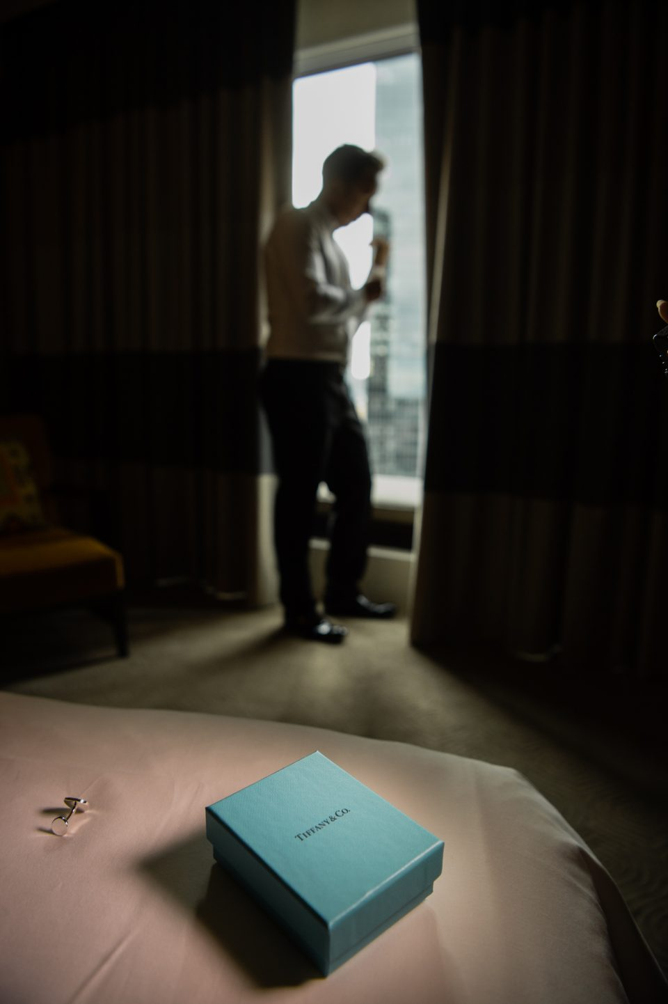 Tiffany & Co. box and cufflink sit on bed in foreground with Groom standing at window doing up cufflink in background
