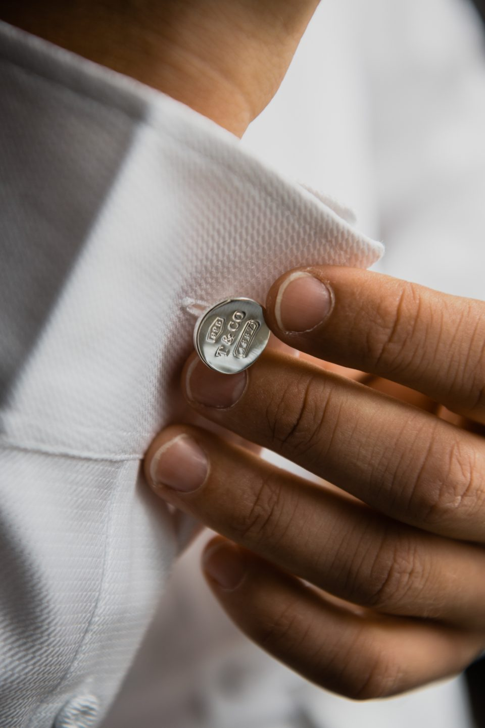 Close up of Grooms hand fixing Tiffany & Co. cufflink in white shirt on wedding day