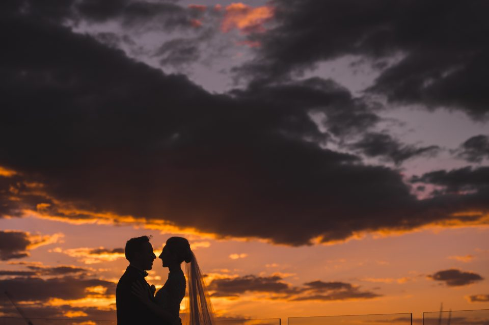Bride and groom silhouette against Sunset with yellow, pink and purple hues through the cloudy sky on roof top of Luminare South Melbourne