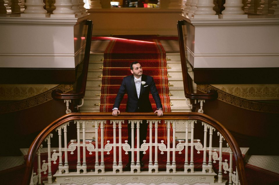 groom waiting for the first look of his bride on grand stair case