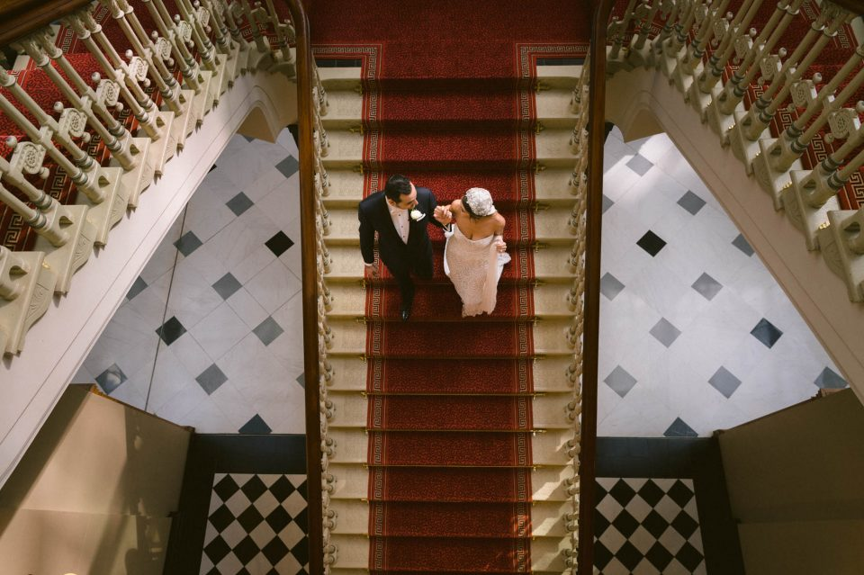 bride and groom on staircase at the fullerton hotel in sydney