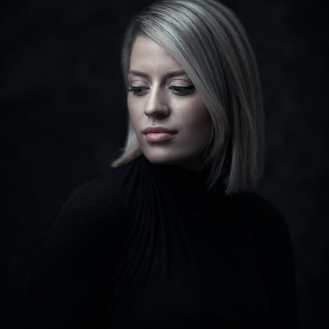 Studio portrait of Cassie, wearing a black turtle-neck top making her blonde hair stand out, taken by Melbourne portrait photographer Rocco Ancora